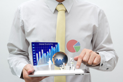 Business man holding tablet pc with graph, chart, pie, globe and building are flying off the screen